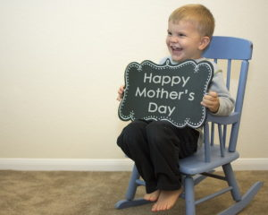 child with 'happy mother's day' message